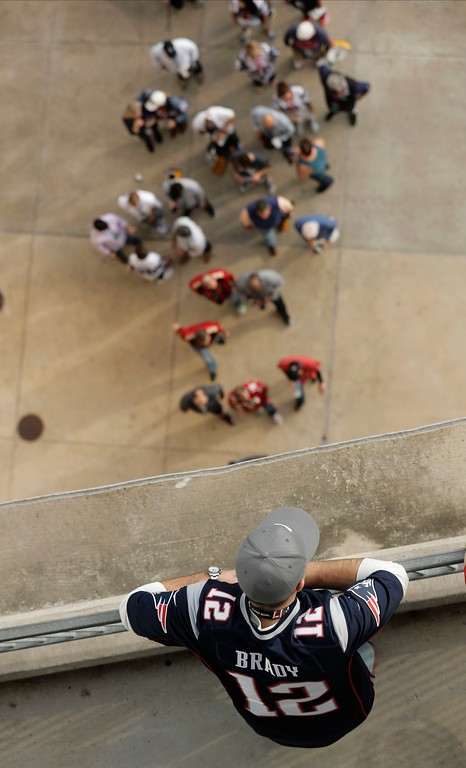 . A New England Patriots fans watches as people arrive before the NFL Super Bowl 51 football game between the Patriots and the Atlanta Falcons, Sunday, Feb. 5, 2017, in Houston. (AP Photo/Charlie Riedel)