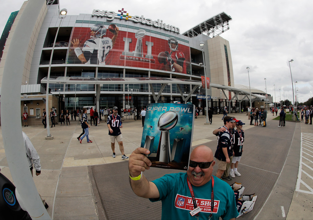 . Michael Alonzo sells programs outside the stadium before the NFL Super Bowl 51 football game between the Atlanta Falcons and the New England Patriots, Sunday, Feb. 5, 2017, in Houston. (AP Photo/Charlie Riedel)