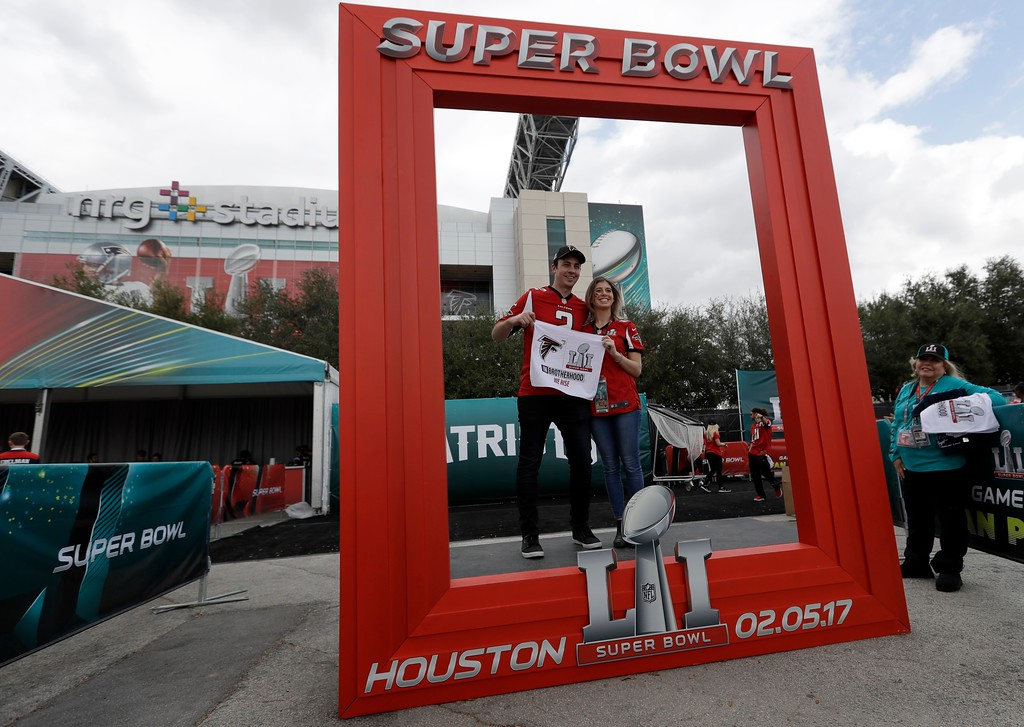. A couple pose for a picture outside NRG Stadium before the NFL Super Bowl 51 football game between the Atlanta Falcons and the New England Patriots Sunday, Feb. 5, 2017, in Houston. (AP Photo/David J. Phillip)