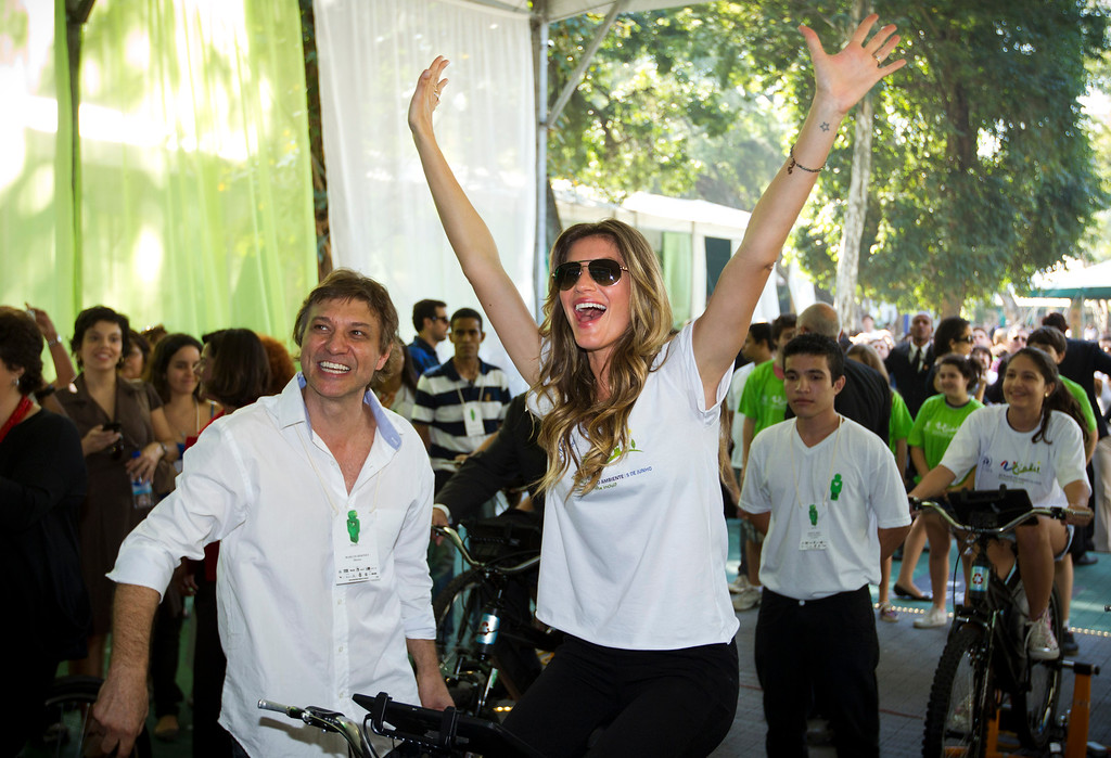 . Gisele Bundchen, Brazilian supermodel and goodwill ambassador for the United Nations Environment Programme (UNEP), raises her arms up into the air while riding a stationary bicycle during the Green Nation Fest environmental show in Rio de Janeiro, Brazil, Monday, June 4, 2012. To the left is Green Nation Fest Marcio Didonet. (AP Photo/Victor R. Caivano)