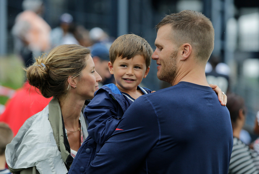 . New England Patriots quarterback Tom Brady and his wife Gisele Bundchen with their son Benjamin Brady after a joint workout with the Tampa Bay Buccaneers at NFL football training camp, in Foxborough, Mass., Tuesday, Aug. 13, 2013. (AP Photo/Charles Krupa)