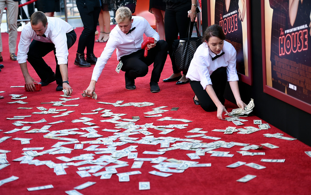". Attendants pick up fake money that was thrown on the red carpet at the premiere of the film ""The House\"" at the TCL Chinese Theatre on Monday, June 26, 2017, in Los Angeles. (Photo by Chris Pizzello/Invision/AP)"