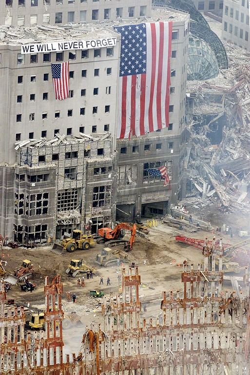 ". American flags and a sign reading ""We Will Never Forget\"" hang from the heavily damaged American Express building on West Street across from the site of the terrorist attack on the World Trade Center in lower Manhattan Monday, Sept. 24, 2001.  Part of the structure of one of the destroyed World Trade Center twin towers can be seen in the foreground. (AP Photo/Roberto Borea)"