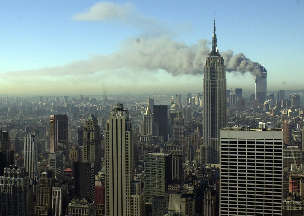 . Plumes of smoke pour from the World Trade Center buildings in New York Tuesday, Sept. 11, 2001. Planes crashed into the upper floors of both World Trade Center towers minutes apart Tuesday in a horrific scene of explosions and fires that left gaping holes in the 110-story buildings. (AP Photo/Patrick Sison)