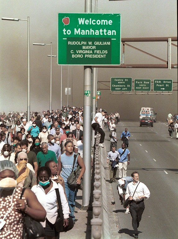 . People flee lower Manhattan across the Brooklyn Bridge in New York, Tuesday, Sept. 11, 2001, following a terrorist attack on the World Trade Center. (AP Photo/Daniel Shanken) MANDATORY CREDIT