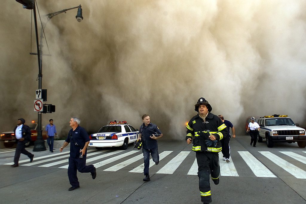 . Policemen and firemen run away from the huge dust cloud caused as the World Trade Center\'s Tower One collapses after terrorists crashed two hijacked planes into the twin towers, September 11, 2001 in New York City. (Photo by Jose Jimenez/Primera Hora/Getty Images)