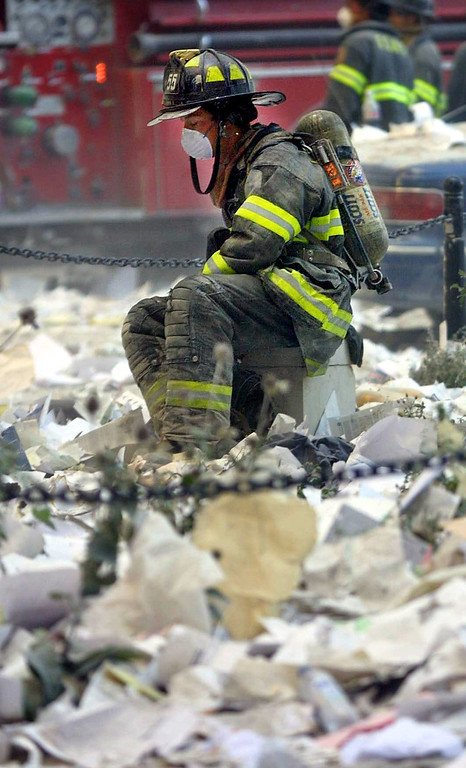 . A firefighter rests in the area where the World Trade Center buildings collapsed September 11, 2001 after two airplanes slammed into the twin towers in a suspected terrorist attack. (Photo by Mario Tama/Getty Images)