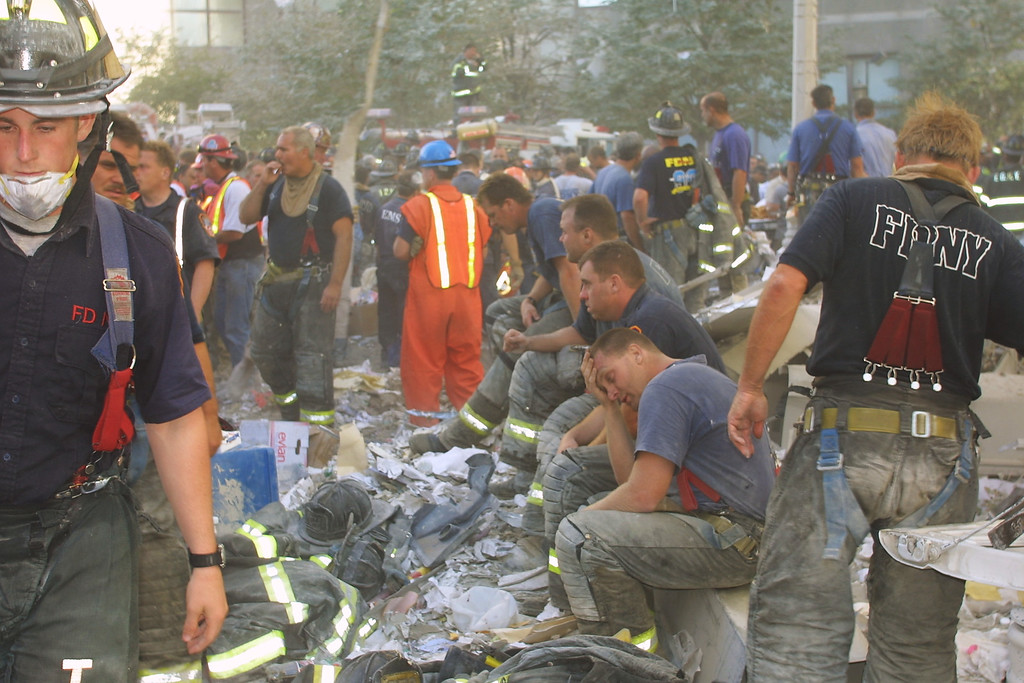 . New York City firefighters rest during rescue operations at the World Trade Center after two hijacked planes crashed into the Twin Towers September 11, 2001 in New York. (Photo by Ron Agam/Getty Images)