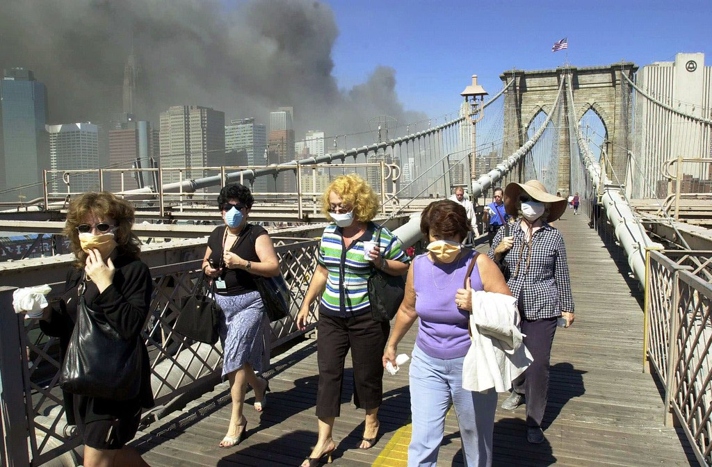 . Women wearing dust masks flee across the Brooklyn Bridge from Manhattan to Brooklyn following the collapse of both World Trade Center towers Tuesday, Sept. 11, 2001 in New York. The towers previously loomed tall in the skyline behind. (AP Photo/Mark Lennihan)