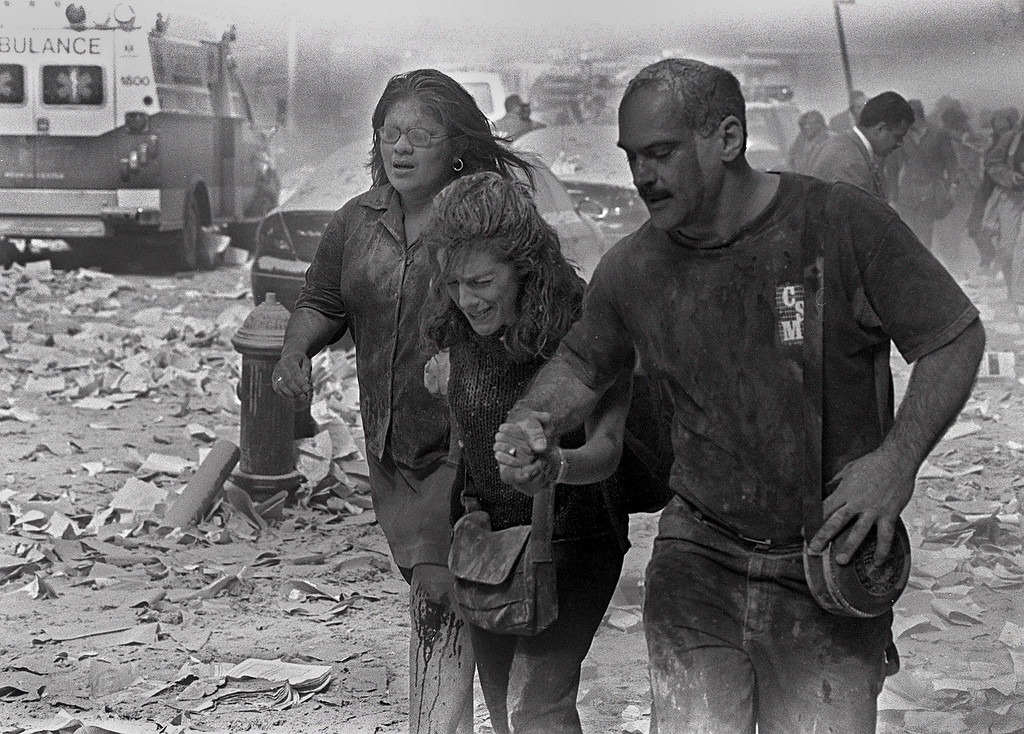. Julie McDermott, center, walks with other victims as they make their way amid debris near the World Trade Center in New York Tuesday Sept. 11, 2001. In one of the most horrifying attacks ever against the United States, terrorists crashed two airliners into the World Trade Center in a deadly series of blows that brought down the twin 110-story towers. (AP Photo/Gulnara Samoilova)