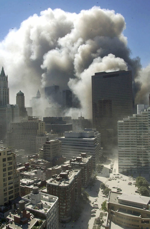 . Smoke rises following the collapse of the World Trade Center towers in New York on Sept. 11, 2001. The skyscraper in the center right of the photo, 7 World Trade Center, also collapsed later on Sept. 11. (AP Photo/Suzanne Plunkett)