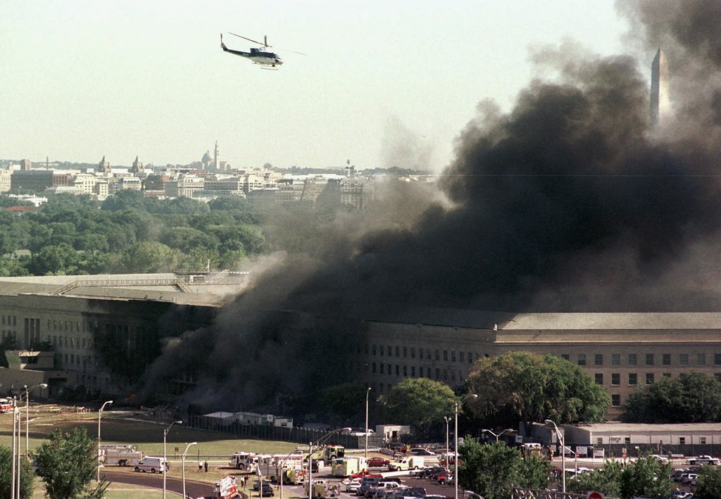 . A helicopter flies over the burning Pentagon Tuesday, Sept. 11, 2001.  The Washington Monument can be seen at right, through the smoke. The White House roof is visible in the trees of Washington at left.  (AP Photo/Tom Horan)