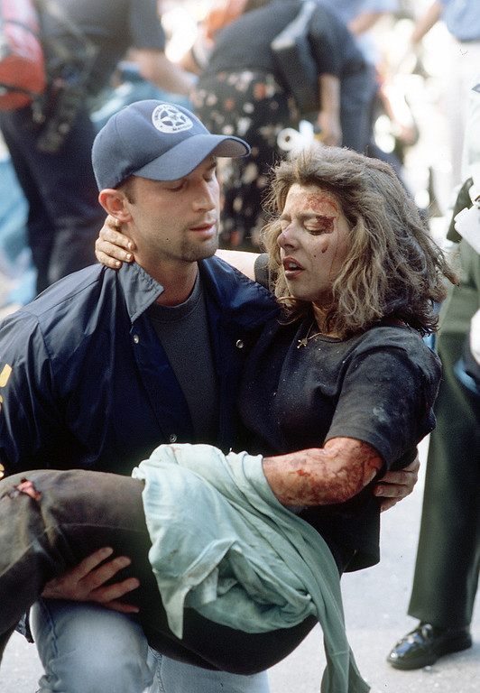 . Deputy U.S. marshal Dominic Guadagnoli helps a women after she was injured in the terrorist attack on the World Trade Center in New York, Tuesday, Sept. 11, 2001. (AP Photo/Gulnara Samoilova)