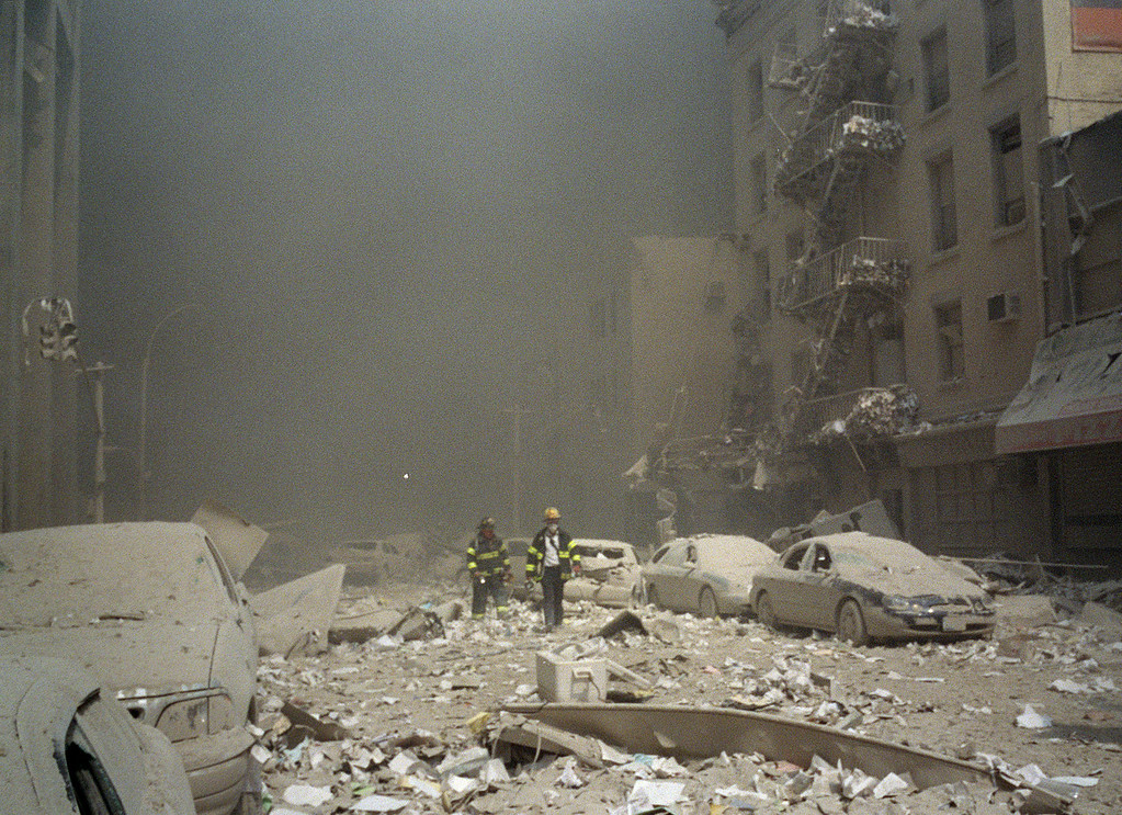 . FIremen walk through a dust and debris covered street in lower Manhattan Tuesday, Sept. 11, 2001, after a terrorist attack at the World Trade Center. Two jet planes were crashed into the twin towers, collapsing them and covering the area with the debris.(AP Photo/Richard Cohen)