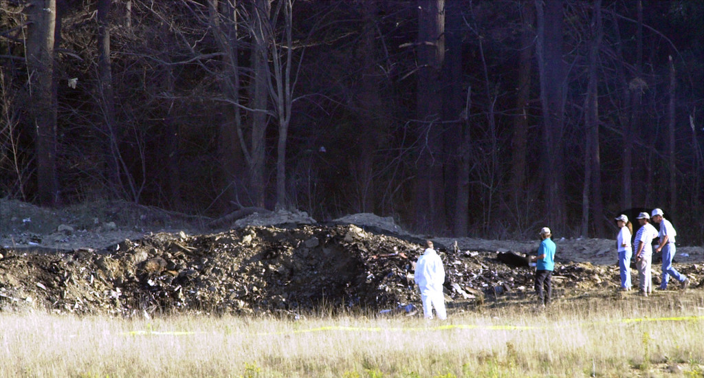. Emergency workers look at the crater created when United Airlines Flight 93 crashed near Shanksville, Pa., on Tuesday, Sept. 11, 2001. Radar showed the San Francisco-bound Boeing 757 from Newark, N.J., had nearly reached Cleveland when it made a sharp left turn and headed back toward Pennsylvania, crashing in a grassy field edged by woods about 80 miles southeast of Pittsburgh.  (AP Photo/Keith Srakocic)