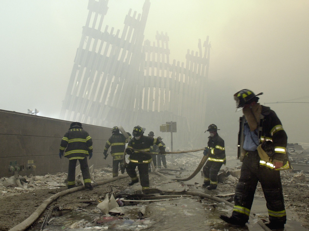. FILE - In this Sept. 11, 2001 file photo, firefighters work beneath the destroyed mullions, the vertical struts which once faced the soaring outer walls of the World Trade Center towers, after a terrorist attack on the twin towers in New York.    (AP Photo/Mark Lennihan)