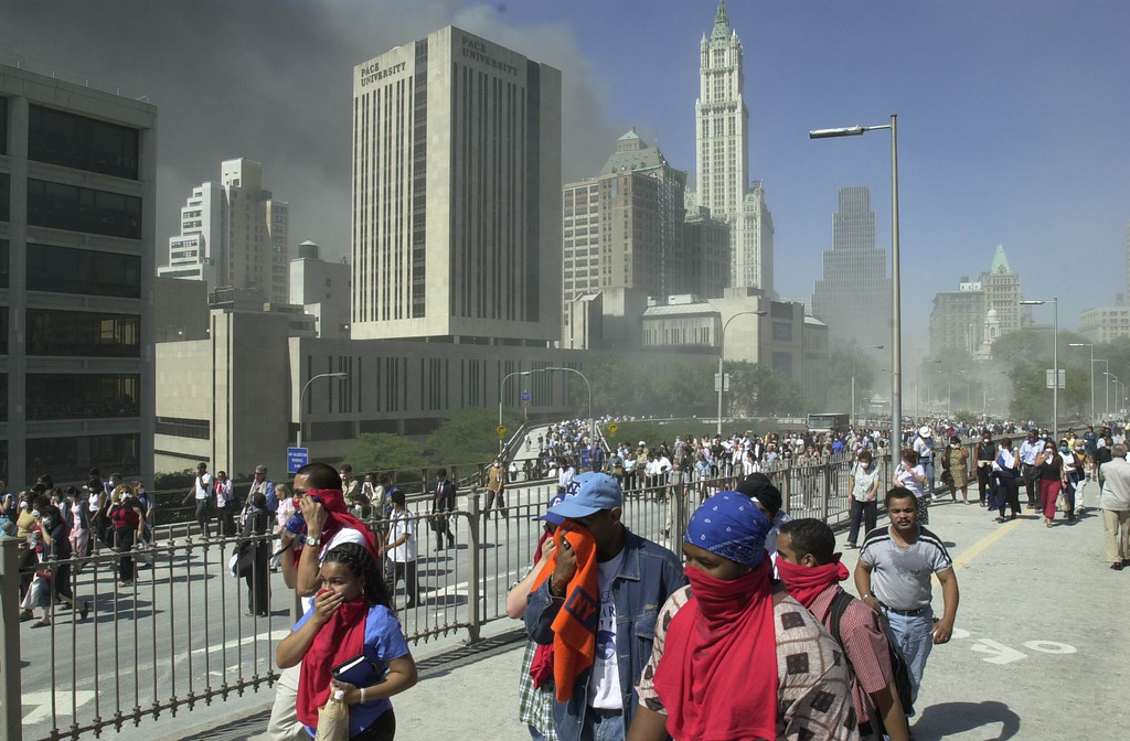 . In this Sept. 11, 2001 photo, people walk to New York\'s Brooklyn Bridge from Manhattan to Brooklyn following the collapse of both World Trade Center towers. (AP Photo/Mark Lennihan)
