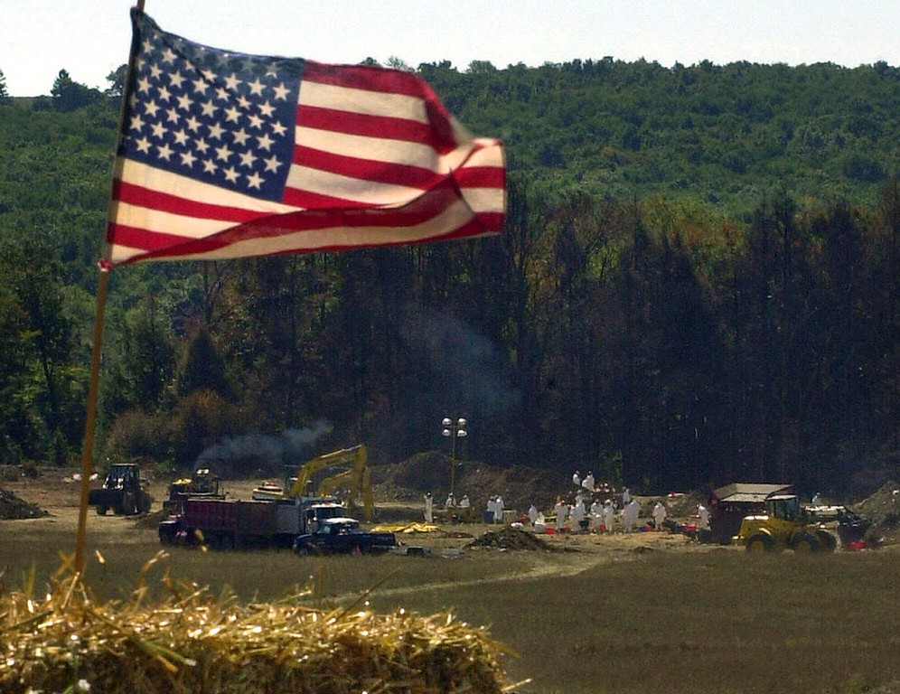 . In this Sept. 16, 2001 file photo an American flag flies from a makeshift altar overlooking the ongoing investigation of the crash of United Airlines Flight 93 in Shanksville, Pa. The plane crashed after being hijacked in the Sept. 11 terrorist attacks. (AP Photo/Gene J. Puskar, File)