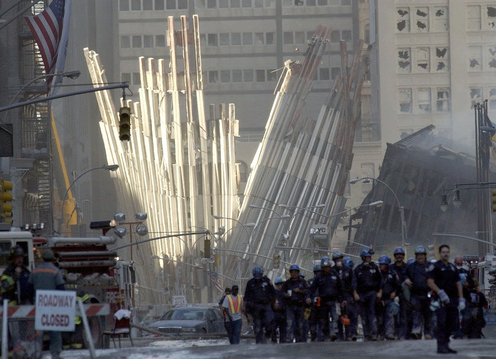 . Workers gather Wednesday, Sept. 12, 2001, to continue work at the site of the attack on the World Trade Center in New York.  A large piece of the facade fallen from the one of the twin towers is in the background. (AP Photo/Amy Sancetta)