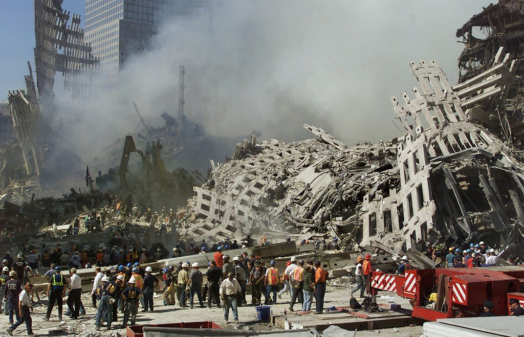 . Rescue workers continue their search as smoke rises from the rubble of the World Trade Center, Thursday, Sept. 13, 2001, in New York. The search for survivors and the recovery of the victims continues since Tuesday\'s terrorist attack. (AP Photo/Beth A. Keiser)