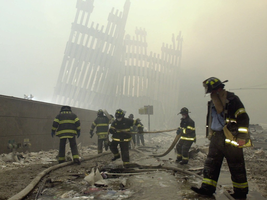 . Firefighters work beneath the destroyed mullions, the vertical struts, of the World Trade Center\'s twin towers after a terrorist attack in New York Tuesday, Sept. 11, 2001. As workers cleared some of the rubble, new crews of firefighters and rescue workers charged into the devastation with shovels, pickaxes and flashlights to look for bodies or survivors. (AP Photo/Mark Lennihan)
