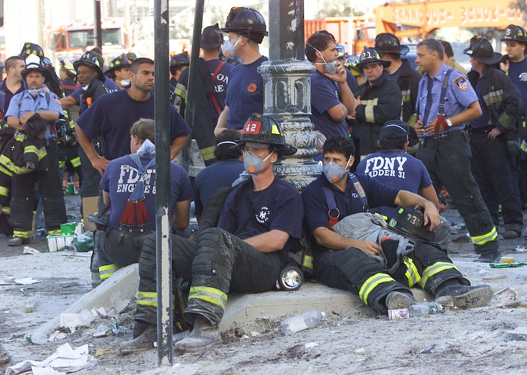 . Firefighters rest as rescue efforts continue at the World Trade Center in New York Wednesday Sept. 12, 2001. Many firemen are missing and feared dead in the rubble from the terrorist attack Tuesday. (AP Photo/ Beth Keiser)