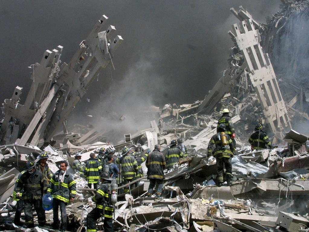. Firefighters make their way through the rubble after two airliners crashed into the World Trade Center in New York bringing down the landmark buildings Tuesday, Sept. 11, 2001. (AP Photo/Shawn Baldwin)