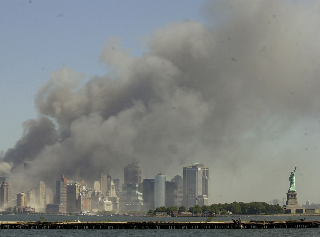 . The Statue of Liberty, right, stands at the entrance to New York Harbor as the twin towers of the World Trade Center burn in this view from Jersey City, N.J., Sept. 11, 2001. (AP Photo/Mike Derer)