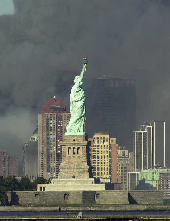 . Thick smoke billows into the sky from the area behind the Statue of Liberty where the World Trade Center towers stood Tuesday, Sept. 11, 2001.  The towers collapsed after terrorists crashed two planes into them Tuesday. (AP Photo/Daniel Hulshizer)
