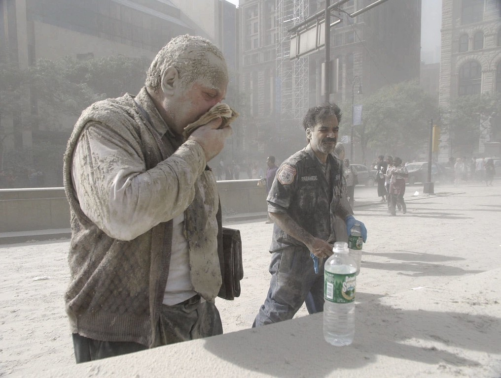 . A man coated with ash and debris from the collapse of the World Trade Center south tower coughs near City Hall in lower Manhattan Sept. 11, 2001. (AP Photo/Amy Sancetta)