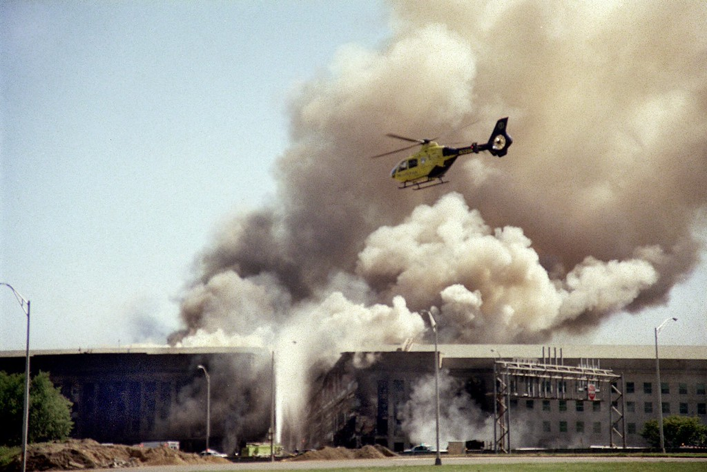 . FILE - In this Sept. 11, 2001 file photo, a helicopter flies over the Pentagon in Washington as smoke billows over the building. (AP Photo/Heesoon Yim, File)