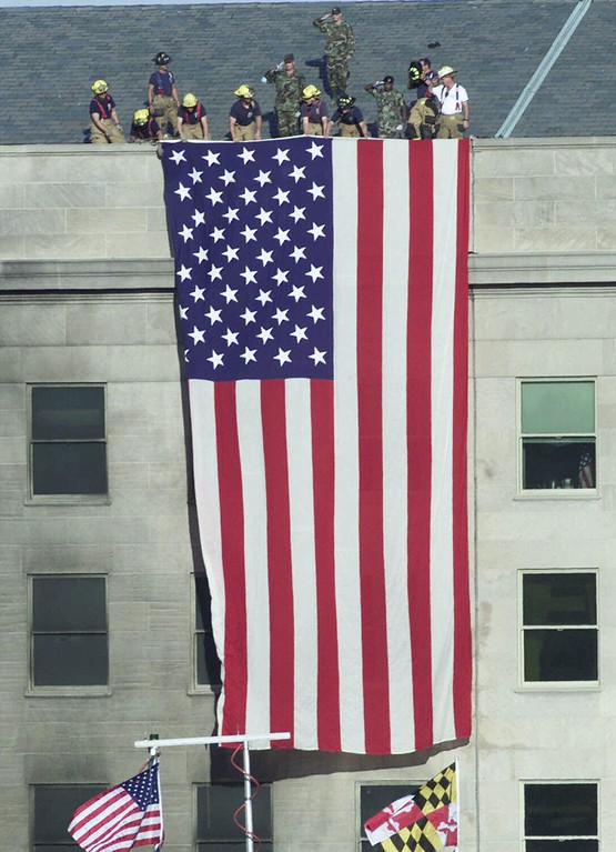 . Firefighters unfurl an American flag from the roof of the Pentagon Wednesday, Sept. 12, 2001, as President Bush visits the area of the Pentagon where an airliner, hijacked by terrorists, crashed into the building on Tuesday. (AP Photo/Ron Edmonds)