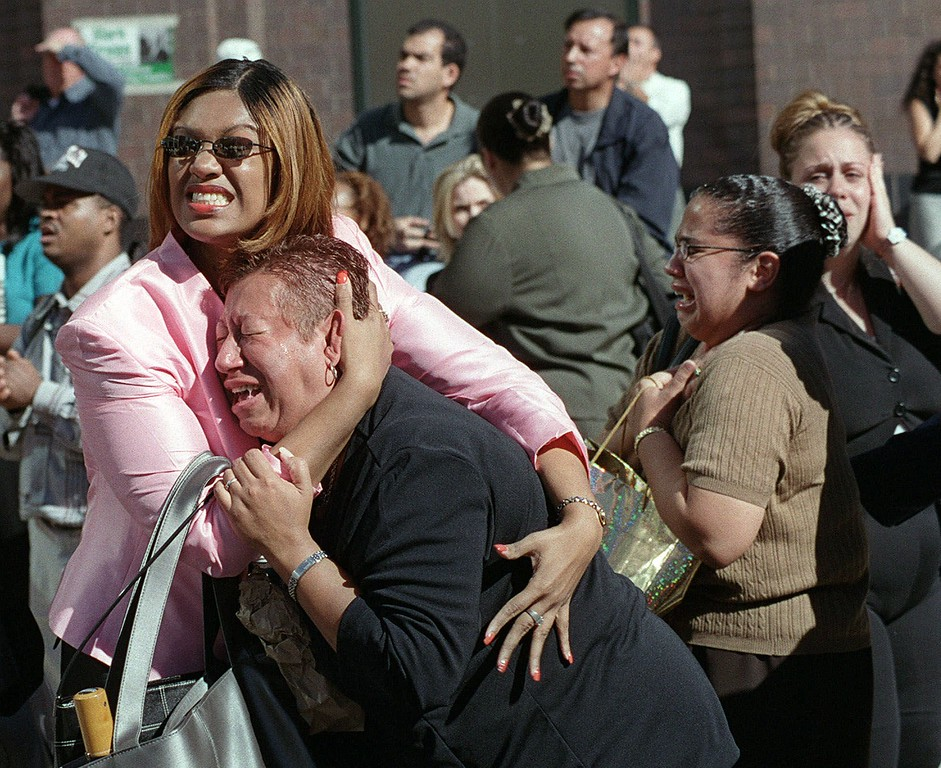 . FILE - In this Tuesday, Sept. 11, 2001 file photo, two women embrace each other as they watch the World Trade Center burn following a terrorist attack on the twin skyscrapers in New York. (AP Photo/Ernesto Mora)