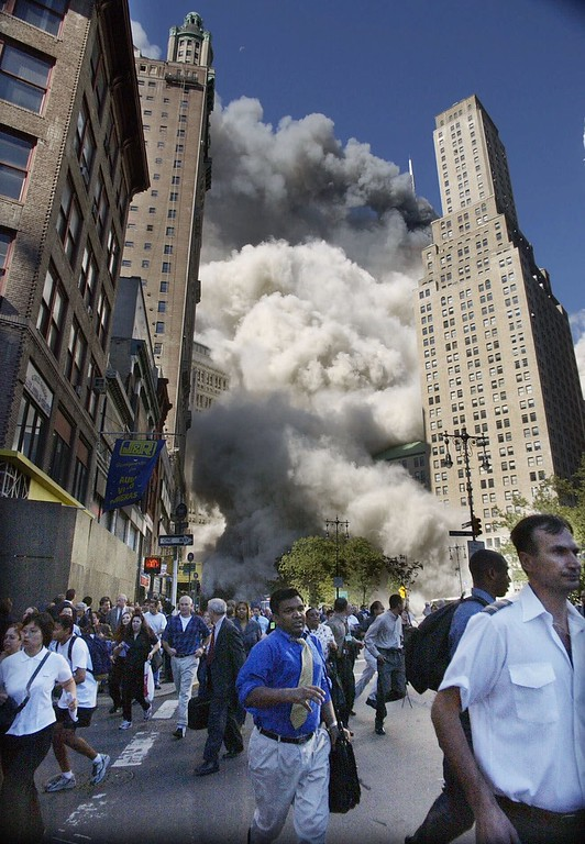 . Pedestrians flee the area of the World Trade Center as the center\'s south tower collapses following a terrorist attack on the New York landmark Tuesday, Sept. 11, 2001. (AP Photo/Amy Sancetta)