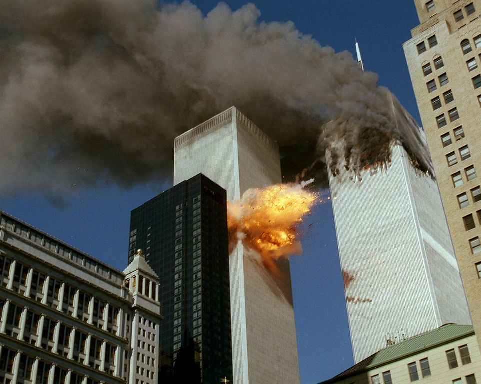 . Smoke pours off one of the towers of the World Trade Center as flames explode from the second one as it is struck by a plane Tuesday, Sept. 11, 2001, after terrorists crashed planes into the buildings.  The attack collapsed both buildings. (AP Photo/Chao Soi Cheong)