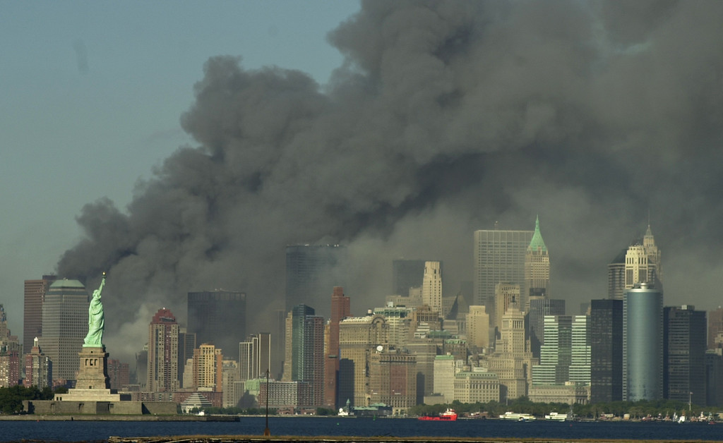 . Thick smoke billows into the sky from the area behind the Statue of Liberty, lower left, where the World Trade Center towers stood, on Tuesday, Sept. 11, 2001.  The towers collapsed after terroists crashed two planes into them. (AP Photo/Daniel Hulshizer)