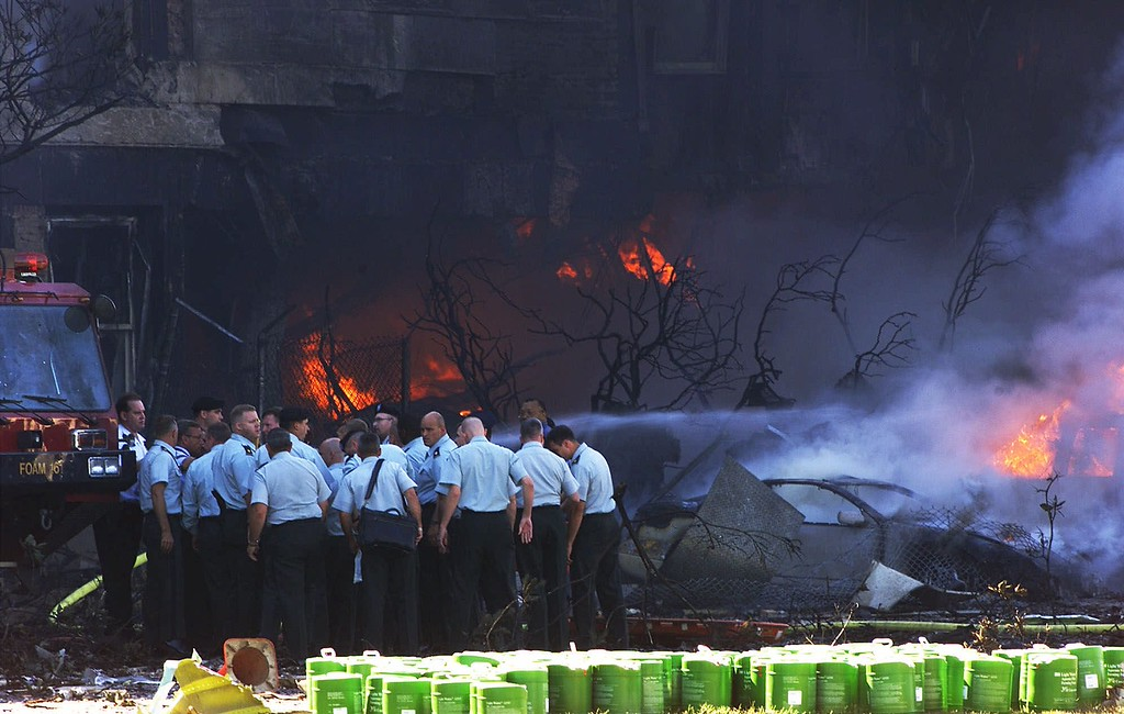. Emergency personnel assess the situation at the Pentagon in Washington after an aircraft crashed into the building Tuesday, Sept. 11, 2001. (AP Photo/Hillery Smith Garrison)