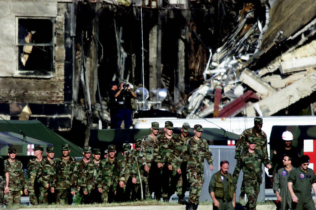 . A large group of soldiers move pass the damage at the Pentagon Wednesday, Sept. 12, 2001, as rescue work continues after a hijacked airliner crashed into the building Tuesday. (AP Photo/Ron Edmonds)