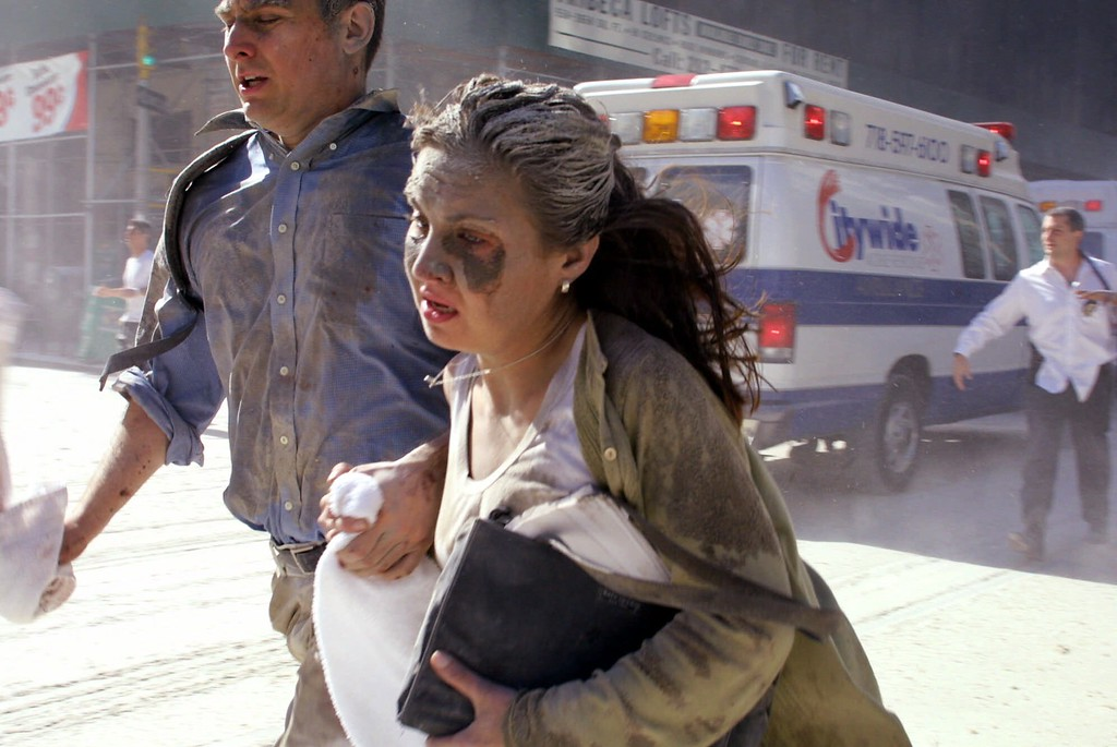 . People flee the scene near New York\'s World Trade Center after terrorists crashed two planes into the towers Tuesday, Sept. 11, 2001. In a horrific sequence of destruction, terrorists hijacked two airliners and crashed them into the World Trade Center in a coordinated series of attacks that brought down the twin 110-story towers. (AP Photo/Diane Bondareff)
