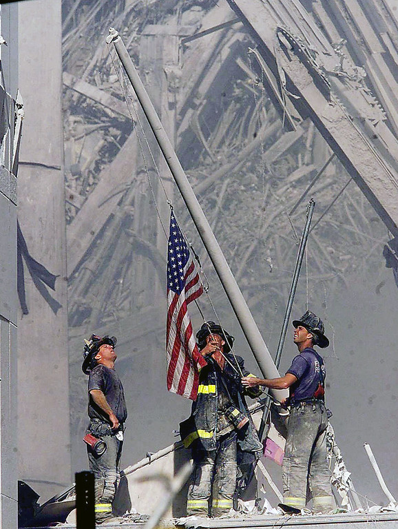 . Brooklyn firefighters George Johnson, left, of ladder 157, Dan McWilliams, center, of ladder 157, and Billy Eisengrein, right, of Rescue 2, raise a flag at the World Trade Center in New York, Sept. 11, 2001, as work at the site continues after hijackers crashed two airliners into the center.   (AP Photo/ Copyright 2001 The Record (Bergen County, NJ), Thomas E. Franklin, Staff Photographer/FILE)