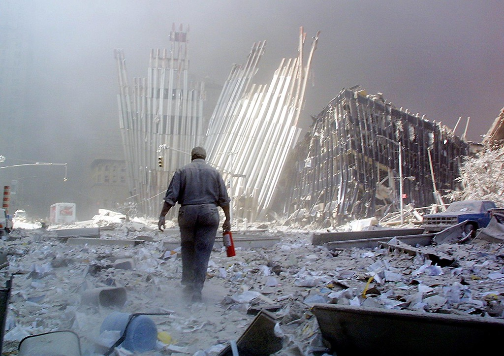 . A man with a fire extinguisher walks through rubble after the collapse of the first World Trade Center Tower 11 September, 2001, in New York. The man was shouting as he walked looking for victims who needed assistance. Both towers collapsed after being hit by hijacked passengers planes.     (DOUG KANTER/AFP/Getty Images)