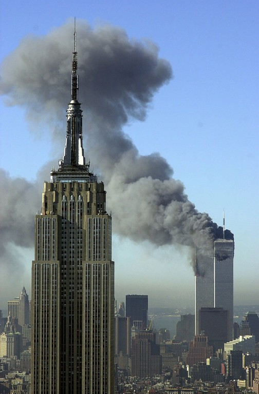 . Plumes of smoke pour from the World Trade Center buildings in New York Tuesday, Sept. 11, 2001. Planes crashed into the upper floors of both World Trade Center towers minutes apart Tuesday in a horrific scene of explosions and fires that lead to the collapse of the 110-story buildings. The Empire State building is seen in the foreground. (AP Photo/Patrick Sison)