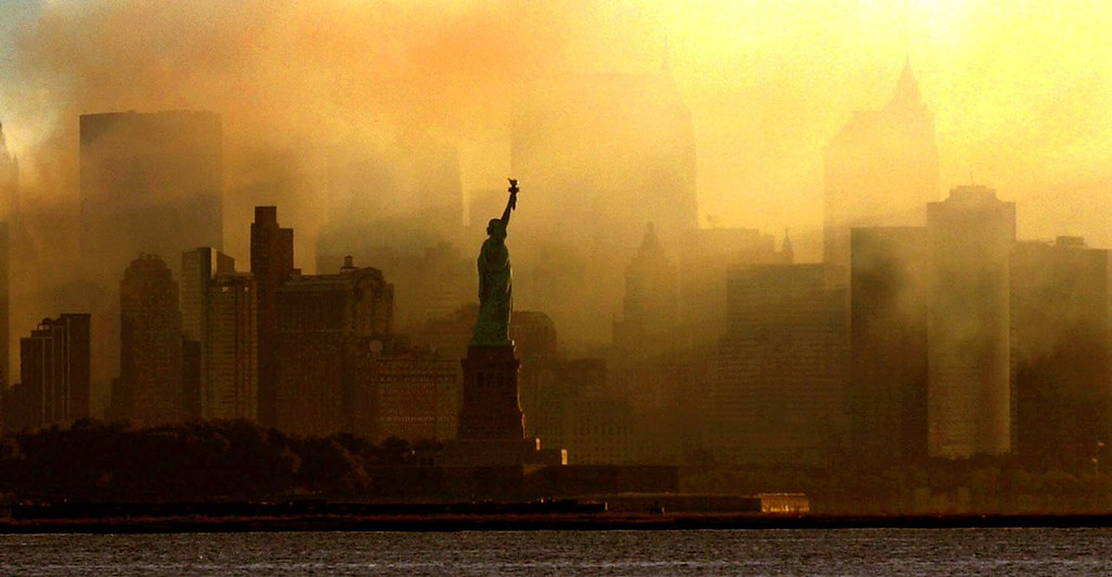 . The Statue of Liberty is seen at first light in this view from Jersey City, N.J., against a smoke-filled backdrop of the lower Manhattan skyline, early Saturday, Sept. 15, 2001.   (AP Photo/Dan Loh)