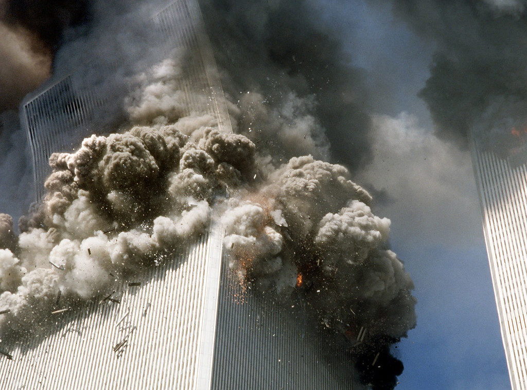 . The south tower of New York\'s World Trade Center, left, begins to collapse after a terrorist attack on the buildings as shown in this Sept. 11, 2001, file photo. Federal investigators believe the second World Trade Center tower fell much more quickly than the first because it faced a more concentrated, intense fire inside, officials said Tuesday. Oct. 19, 2004.    (AP Photo/Gulnara Samoilova, FILE)