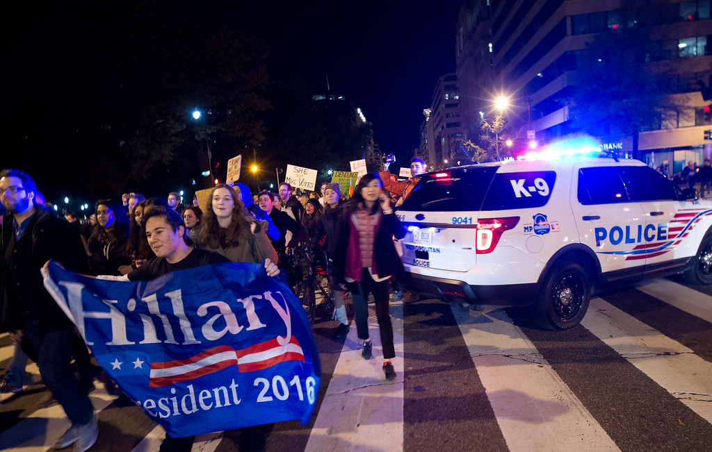 . Demonstrators holds banners as they protest during a march in downtown Washington in opposition of President-elect Donald Trump, Saturday, Nov. 12, 2016. Tens of thousands of people marched in streets across the United States on Saturday, staging the fourth day of protests of Trump\'s surprise victory as president. (AP Photo/Jose Luis Magana)