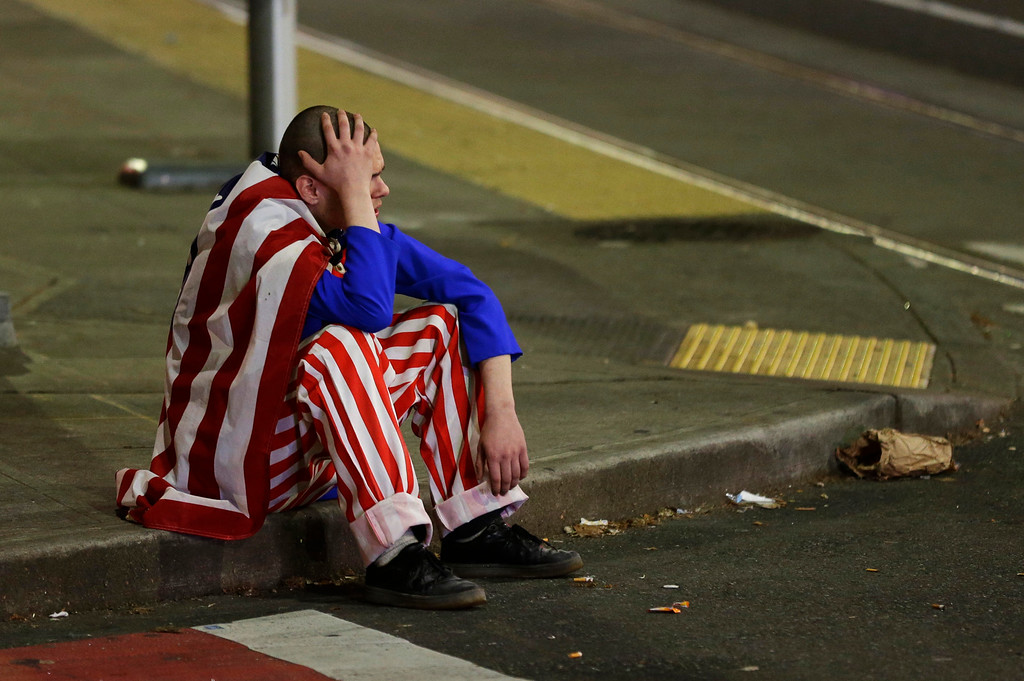. A man dressed in red-white-and-blue sits on the curb during a protest against President-elect Donald Trump, Wednesday, Nov. 9, 2016, in Seattle\'s Capitol Hill neighborhood. (AP Photo/Ted S. Warren)
