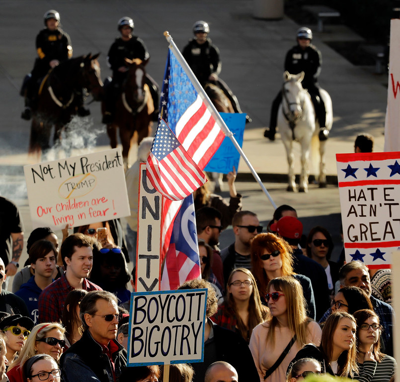 . People protest against the election of President-elect Donald Trump Saturday, Nov. 12, 2016, in front of City Hall in Kansas City, Mo. Thousands took to the streets Saturday across the United States as demonstrations against Trump continued in New York, Chicago, Los Angeles and beyond. (AP Photo/Charlie Riedel)
