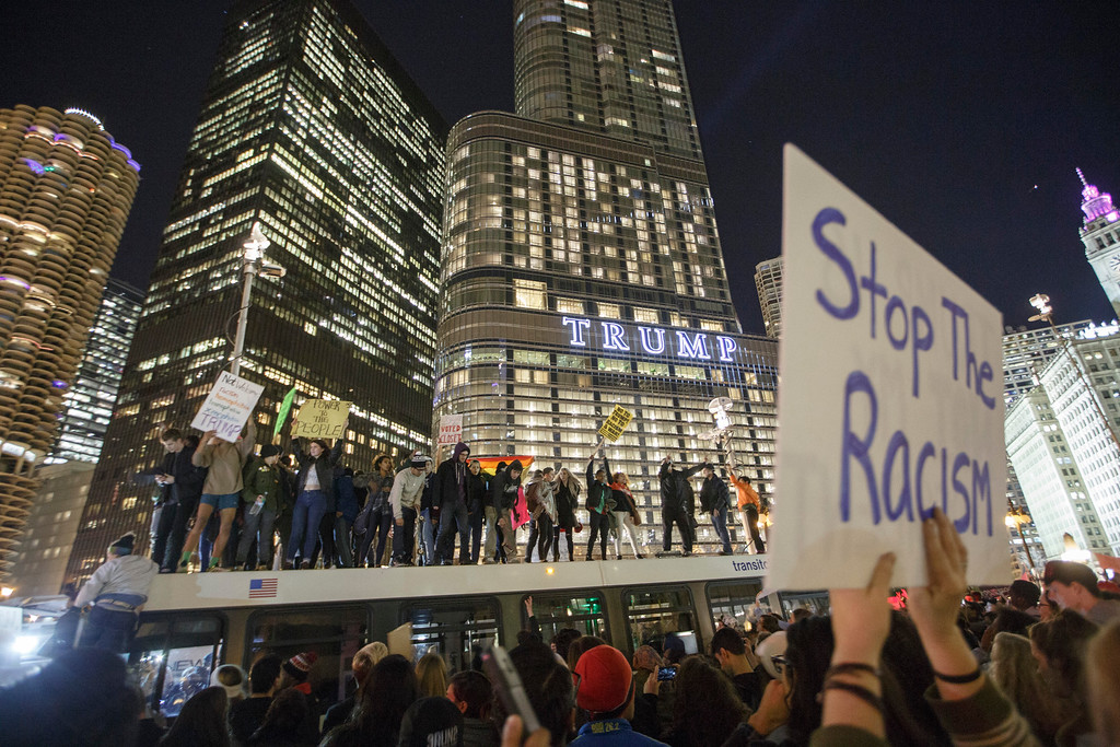 . CHICAGO, IL - NOVEMBER 09: Demonstrators protest on top of a bus outside of the Trump Tower November 9, 2016 in Chicago, Illinois. Thousands of people across the United States took to the streets in protest a day after Republican Donald Trump was elected president, defeating Democrat Hillary Clinton. (Photo by John Gress/Getty Images)