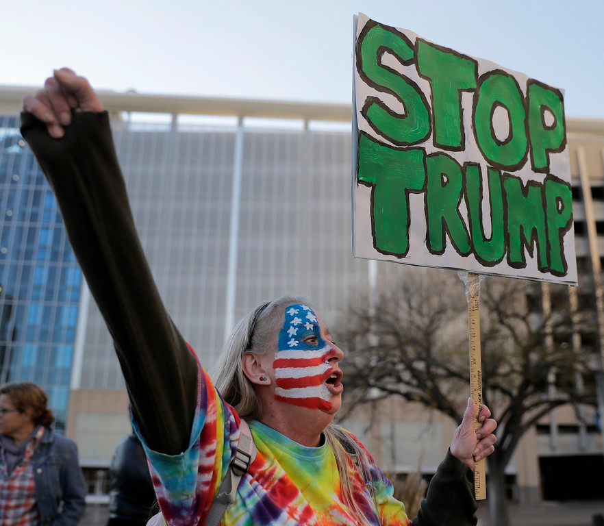. Mary Johnson protests against the election of President-elect Donald Trump Saturday, Nov. 12, 2016, in front of City Hall in Kansas City, Mo. (AP Photo/Charlie Riedel)