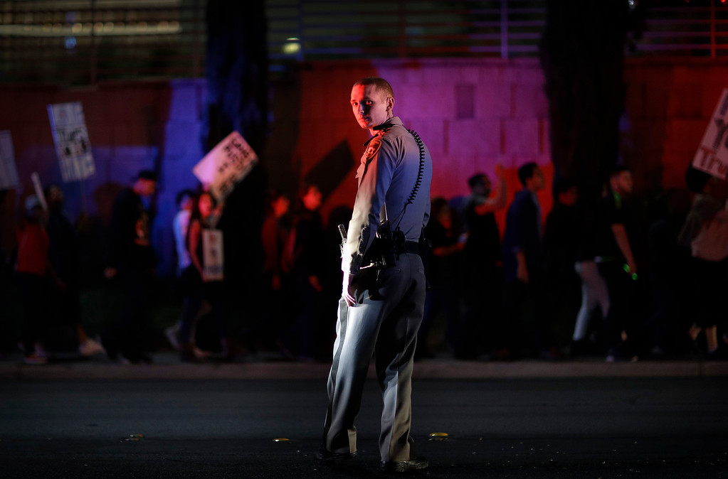 . A Las Vegas police officer stands on duty as protesters against President-elect Donald Trump march near the Las Vegas Strip, Saturday, Nov. 12, 2016, in Las Vegas. Tens of thousands of people marched in streets across the United States on Saturday, staging the fourth day of protests of Trump\'s surprise victory as president. (AP Photo/John Locher)